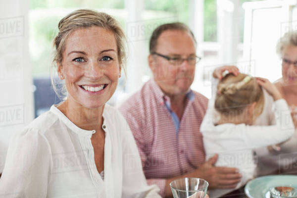 Portrait of smiling woman sitting at dining table with family Royalty-free stock photo