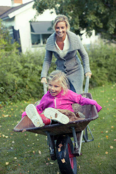 Playful mother pushing daughter on wheelbarrow at yard Royalty-free stock photo