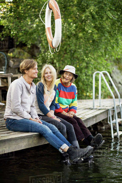 Three generation females sitting on pier Royalty-free stock photo