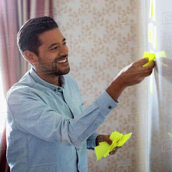 Smiling businessman removing memo notes from whiteboard in office Royalty-free stock photo
