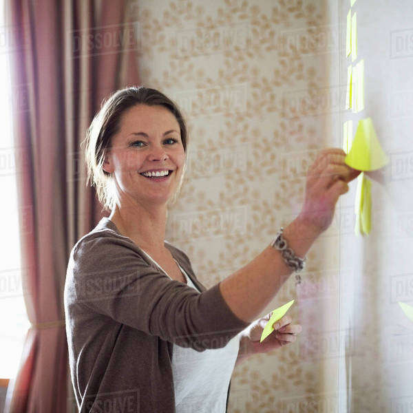 Portrait of businesswoman sticking memo notes on whiteboard Royalty-free stock photo
