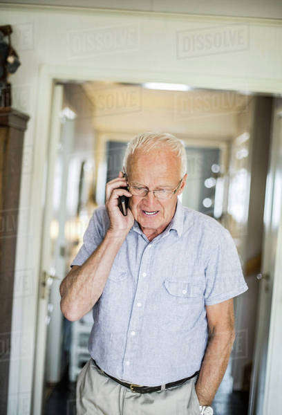 Senior man answering mobile phone at home Royalty-free stock photo