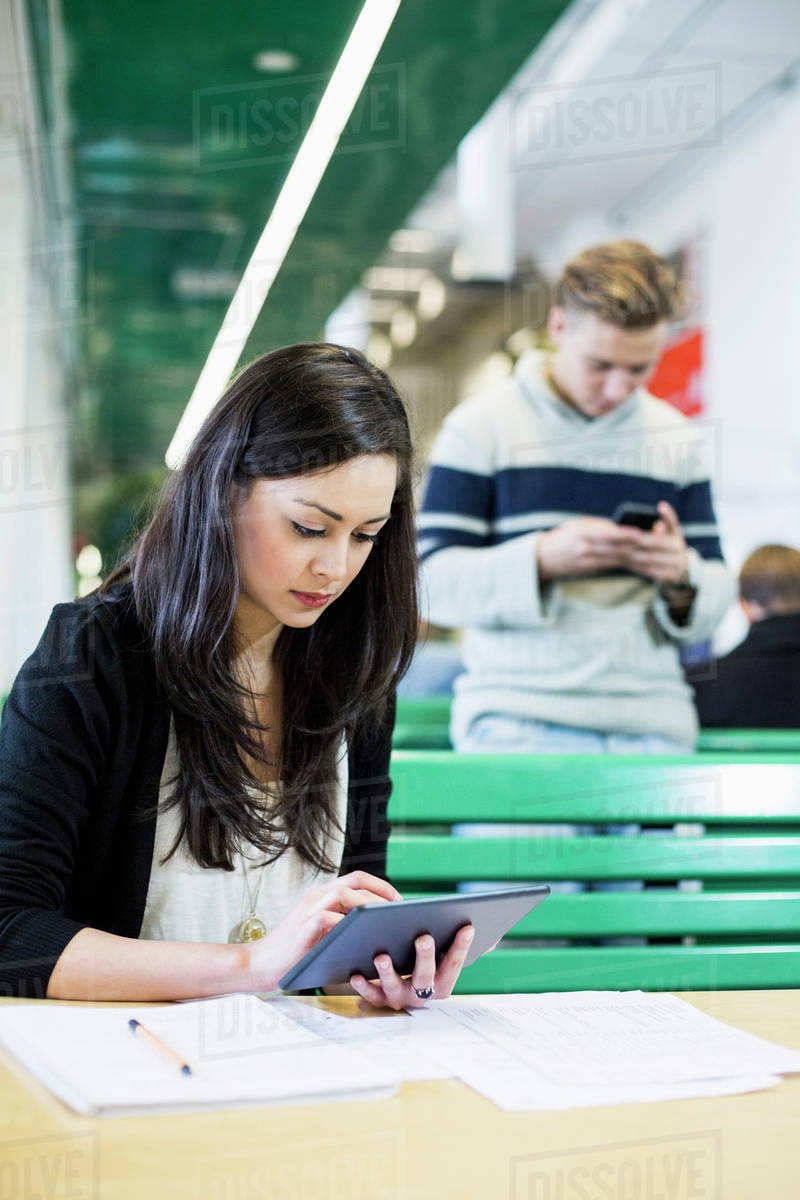 Female university student using digital tablet with friend in background Royalty-free stock photo