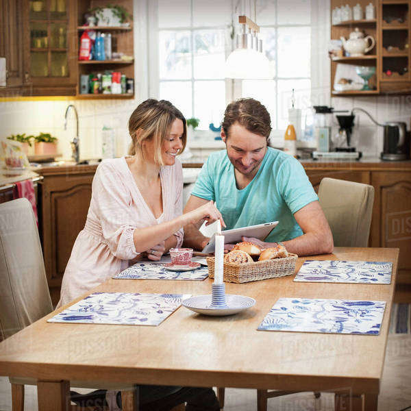 Smiling couple using digital tablet at dining table in kitchen Royalty-free stock photo