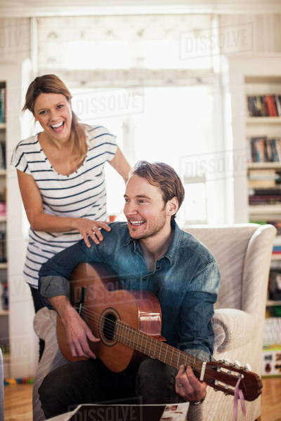 Happy man playing guitar for woman in house Royalty-free stock photo
