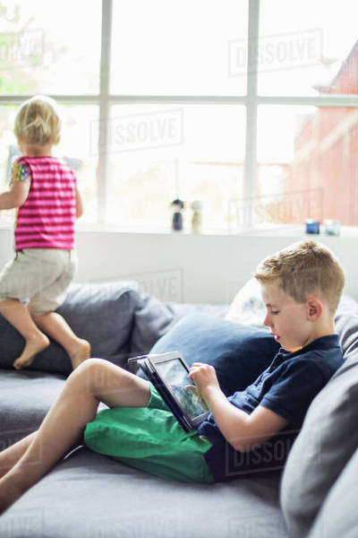 Boy using digital tablet on sofa with sister playing in background Royalty-free stock photo