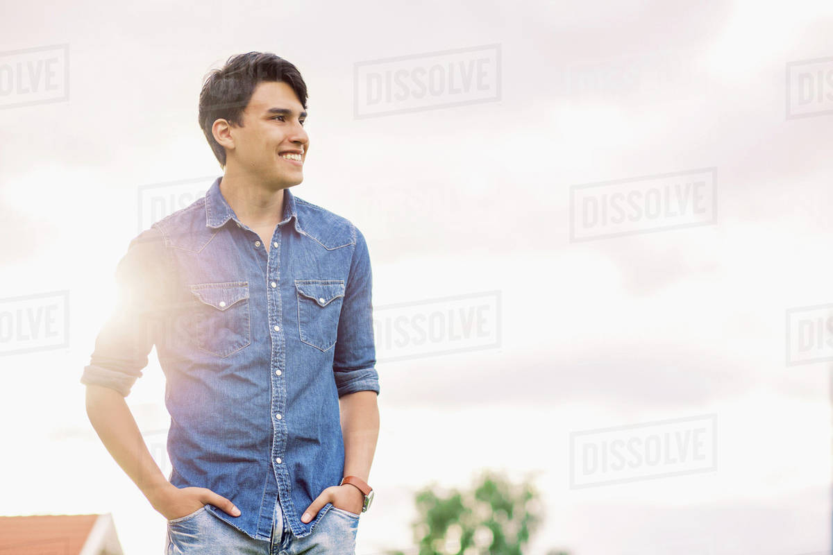 Happy young man with hands in pockets standing against sky Royalty-free stock photo