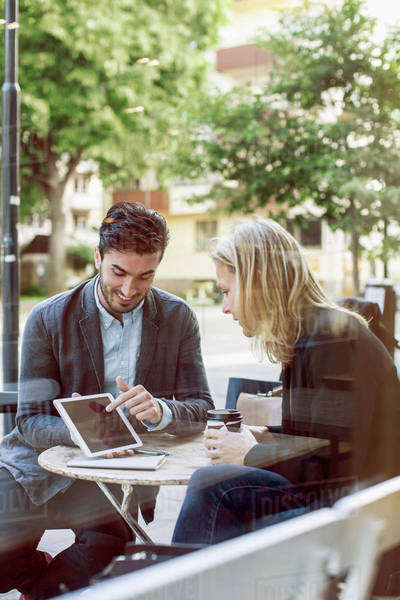 Business colleagues discussing over digital tablet at sidewalk cafe Royalty-free stock photo