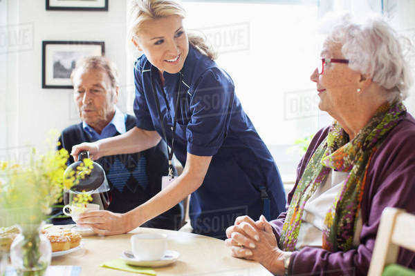Happy female caretaker serving coffee to senior people at nursing home Royalty-free stock photo