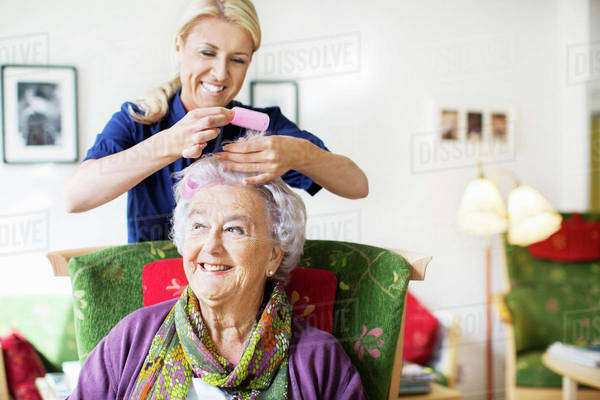 Happy female caretaker putting curlers to senior woman's hair at nursing home Royalty-free stock photo