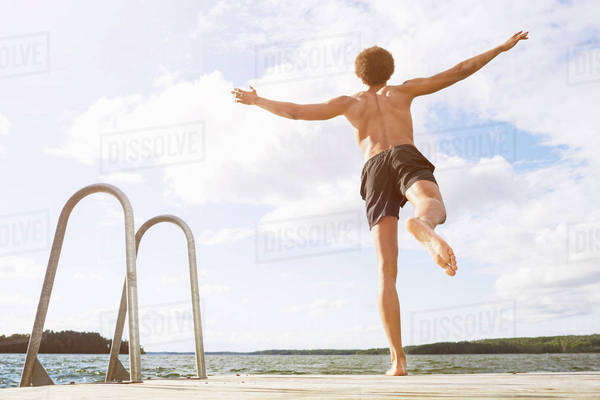 Full length rear view of man diving into lake Royalty-free stock photo