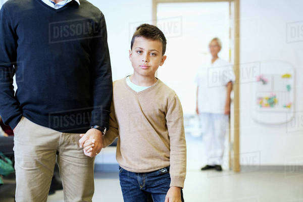Portrait of boy holding father's hand with nurse in background at orthopedic clinic Royalty-free stock photo