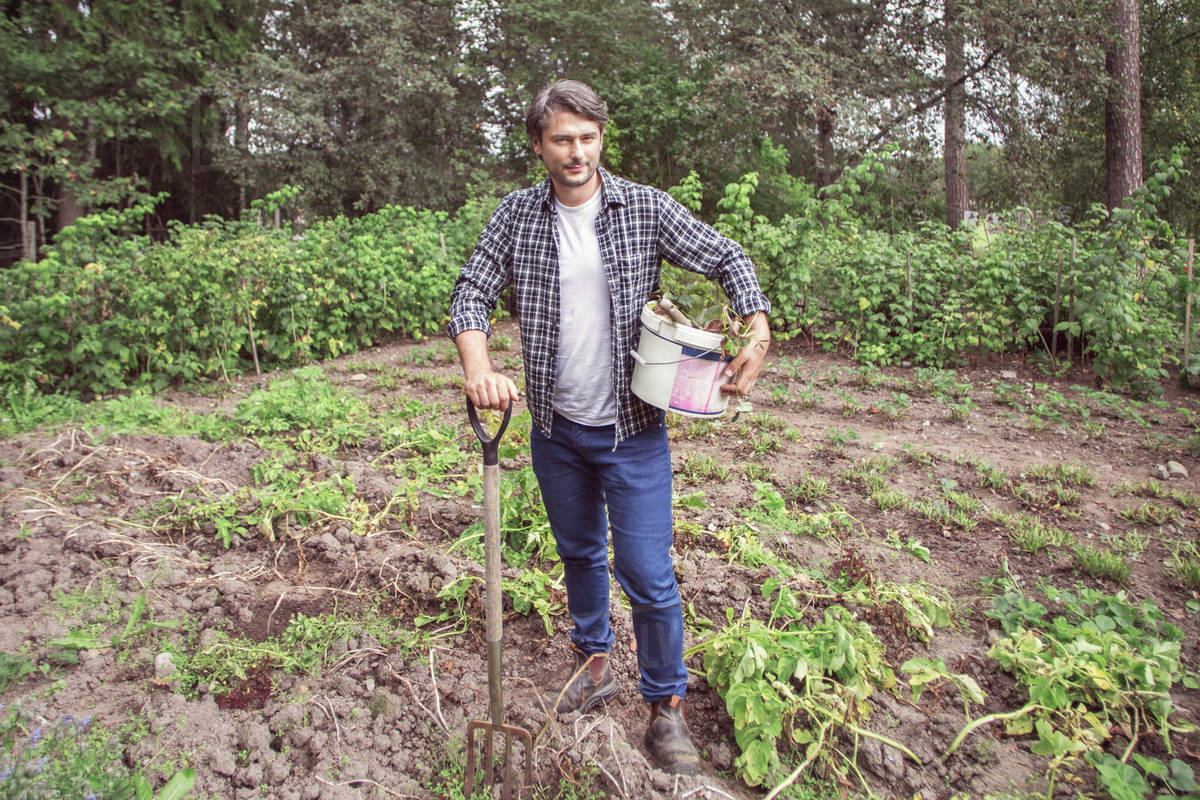Full Length Portrait Of Confident Man With Gardening Fork And Bucket At  Organic Farm