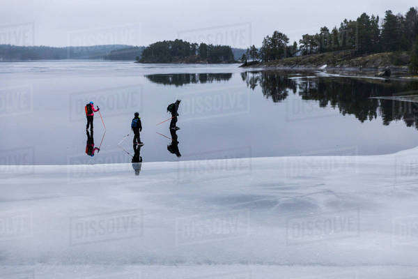 Father and children ice-skating on frozen lake Royalty-free stock photo