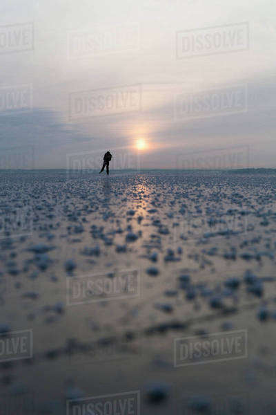 Distant view of woman ice-skating on frozen lake during sunset Royalty-free stock photo