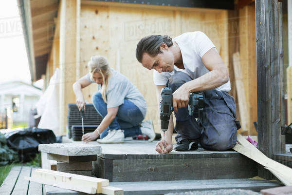 Couple working outside house during home improvement Royalty-free stock photo