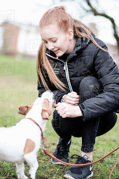 Teenage girl playing with puppy at park Royalty-free stock photo