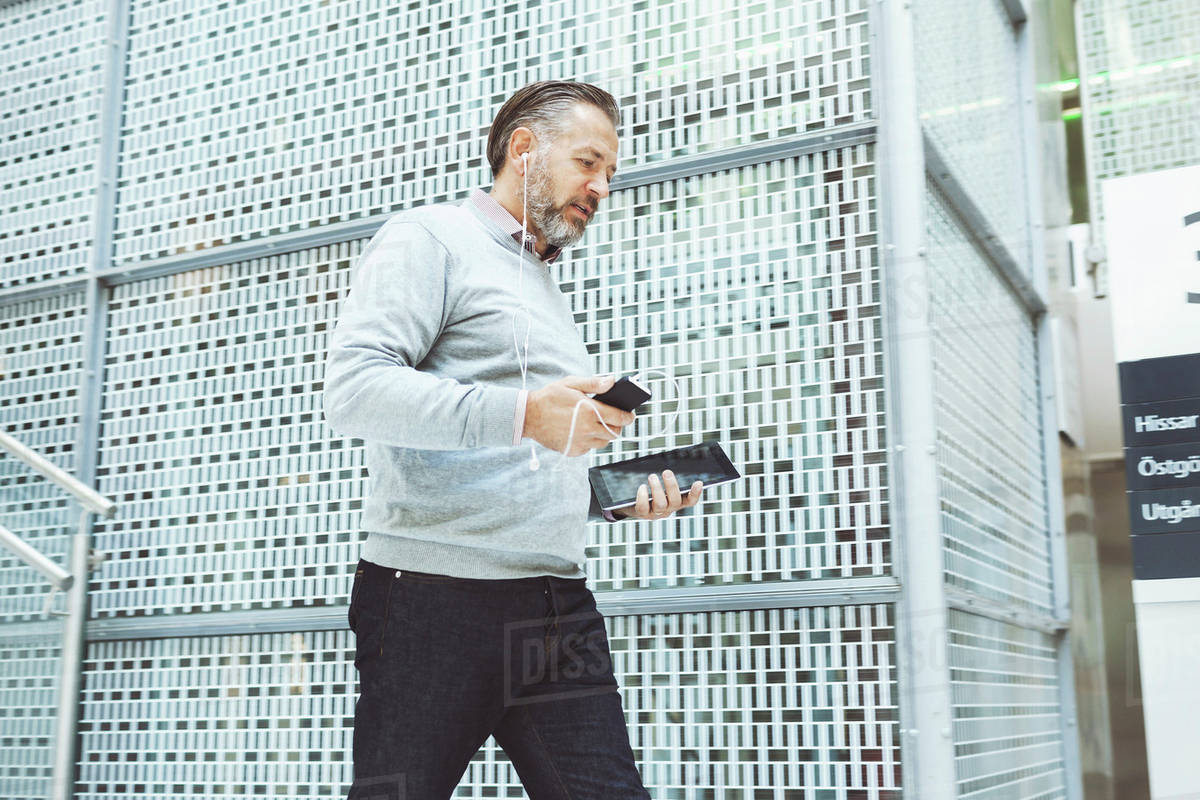 Businessman with digital tablet listening music though mobile phone while walking in office Royalty-free stock photo