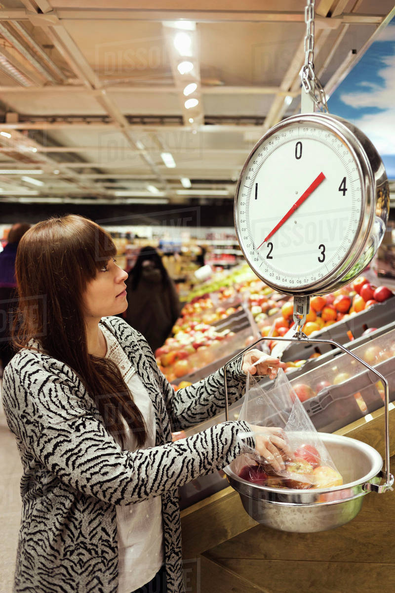 Woman looking at weight scale while weighing apples at supermarket stock  photo