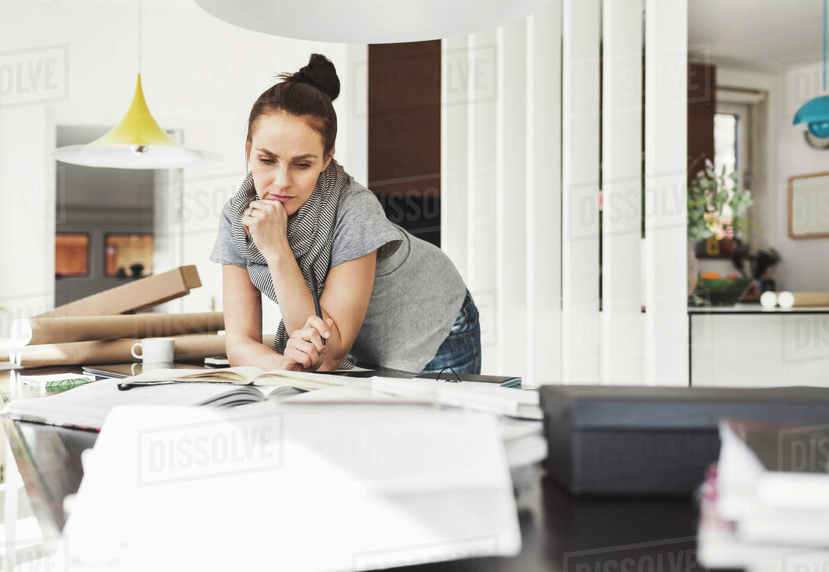 Thoughtful female architect leaning on table at home office - Stock ...