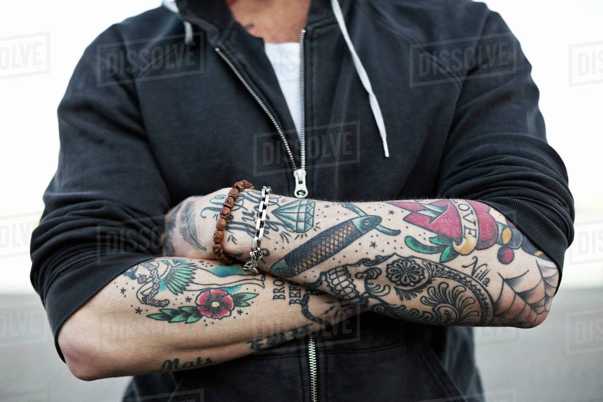 Midsection Of A Tattooed Man With Arms Crossed Stock Photo