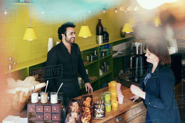 High angle view of happy customer and owner standing in coffee shop Royalty-free stock photo