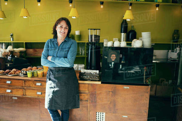 Portrait of confident female owner standing in coffee shop Royalty-free stock photo