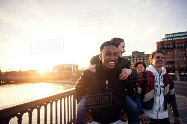 Smiling teenager piggybacking girl while walking with friends by canal Royalty-free stock photo
