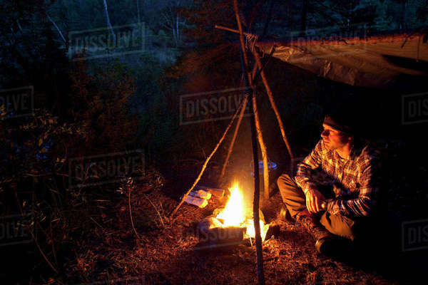 Man sitting by bonfire in forest at night Royalty-free stock photo