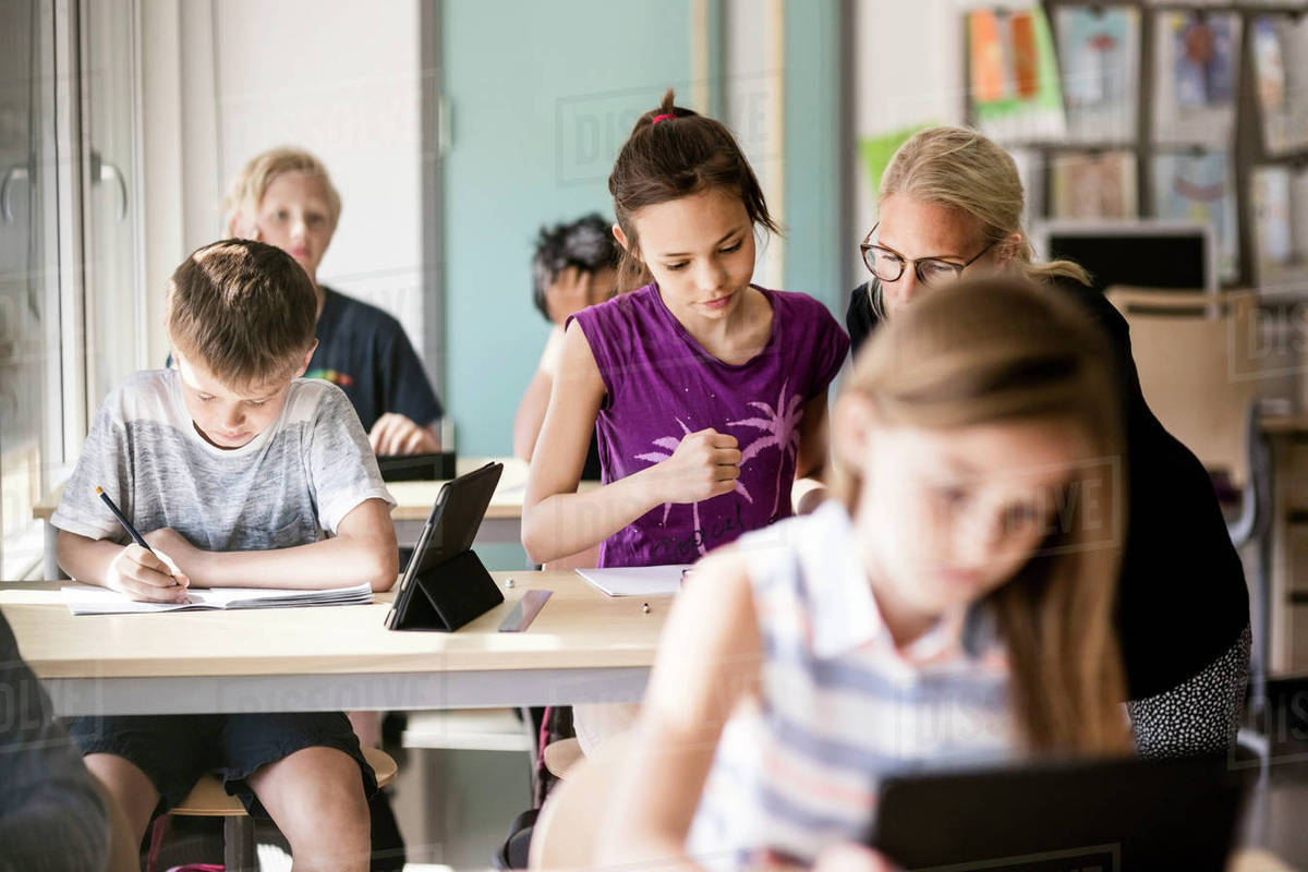 Teacher Assisting Schoolgirl By Boy In Classroom