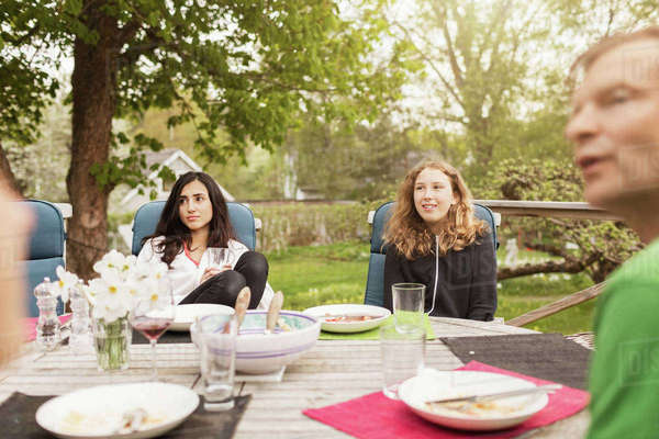 Teenage girls sitting with father at table in yard Royalty-free stock photo