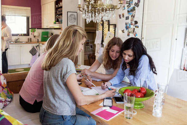 Teenage girls discussing while studying at table Royalty-free stock photo