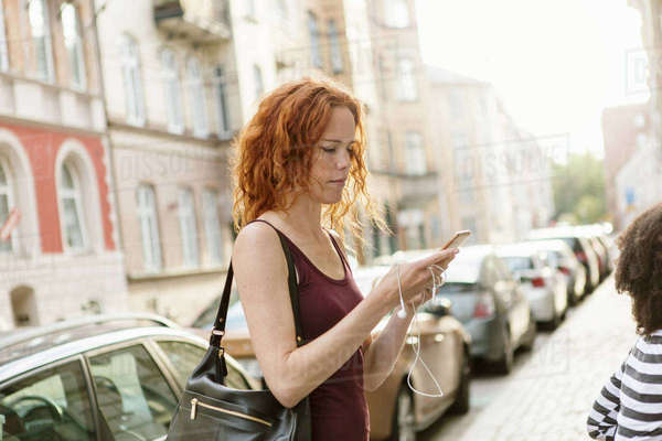 Woman using mobile phone on sidewalk in city Royalty-free stock photo