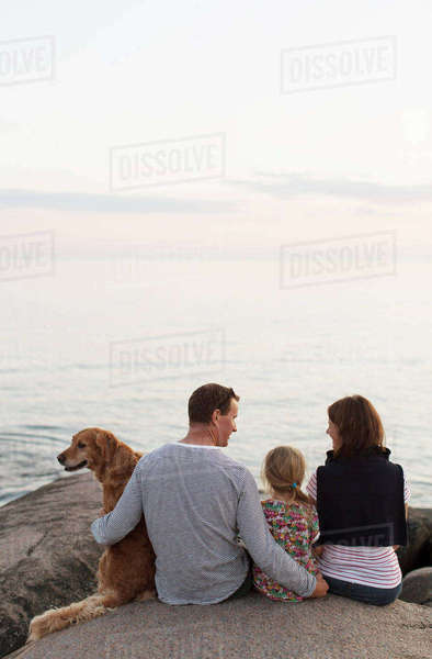 Rear view of family sitting with dog on rock formation against sky Royalty-free stock photo