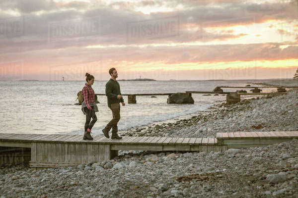 Side view of couple walking on jetty at beach against sky during sunset Royalty-free stock photo