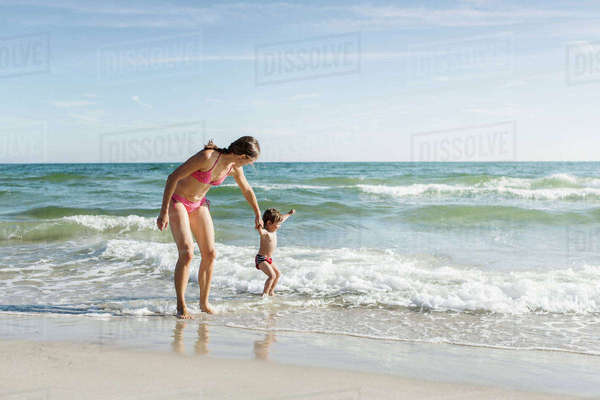 Mother with daughter enjoying on beach against sky during sunny day Royalty-free stock photo
