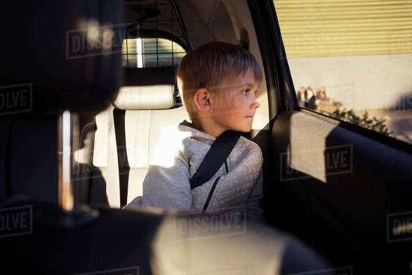 Boy sitting in electric car looking through window Royalty-free stock photo