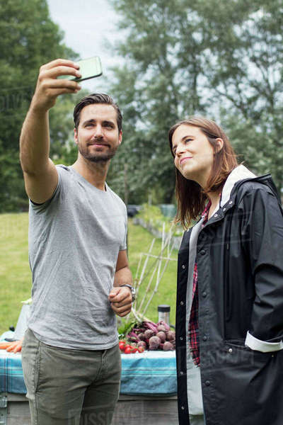 Mid adult couple taking selfie through mobile phone in urban garden Royalty-free stock photo