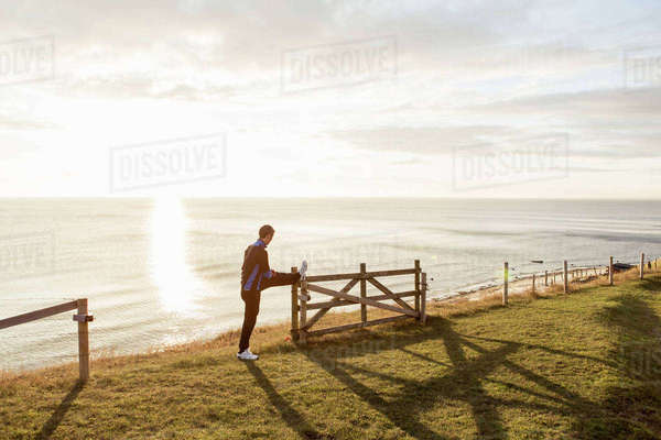 Full length of man stretching leg on fence at beach during sunny day Royalty-free stock photo