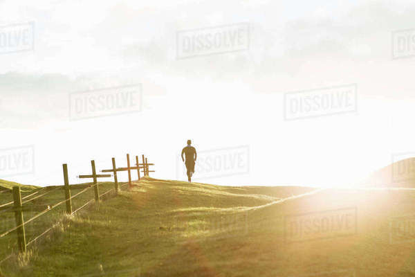 Distant view of man jogging on grassy field against sky during sunny day Royalty-free stock photo