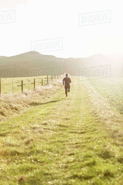 Rear view of man jogging on grassy field during sunny day against clear sky Royalty-free stock photo