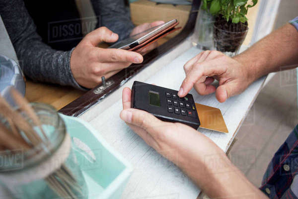 High angle view of customer paying through card reader while owner using digital tablet at food truck Royalty-free stock photo