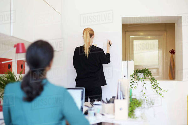 Rear view of businesswoman writing on whiteboard with colleague in foreground at office Royalty-free stock photo