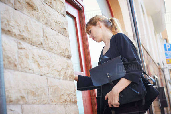 Low angle view of businesswoman with bags entering into office Royalty-free stock photo