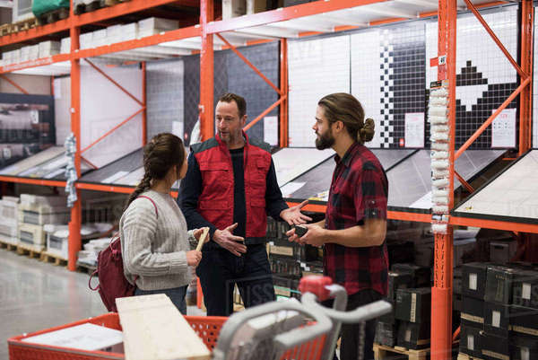 Salesman discussing with couple by shelves at hardware store Royalty-free stock photo