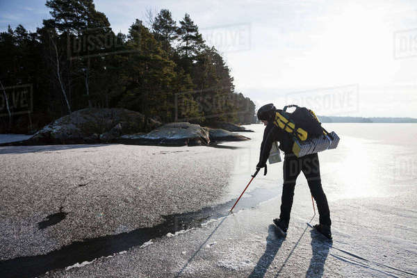 Full length of mature man dipping hiking pole in water while standing on frozen lake Royalty-free stock photo