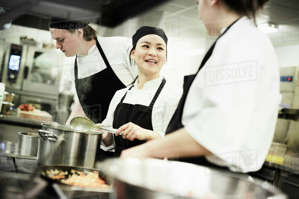 Female chef cooking food while talking with colleague in commercial ...