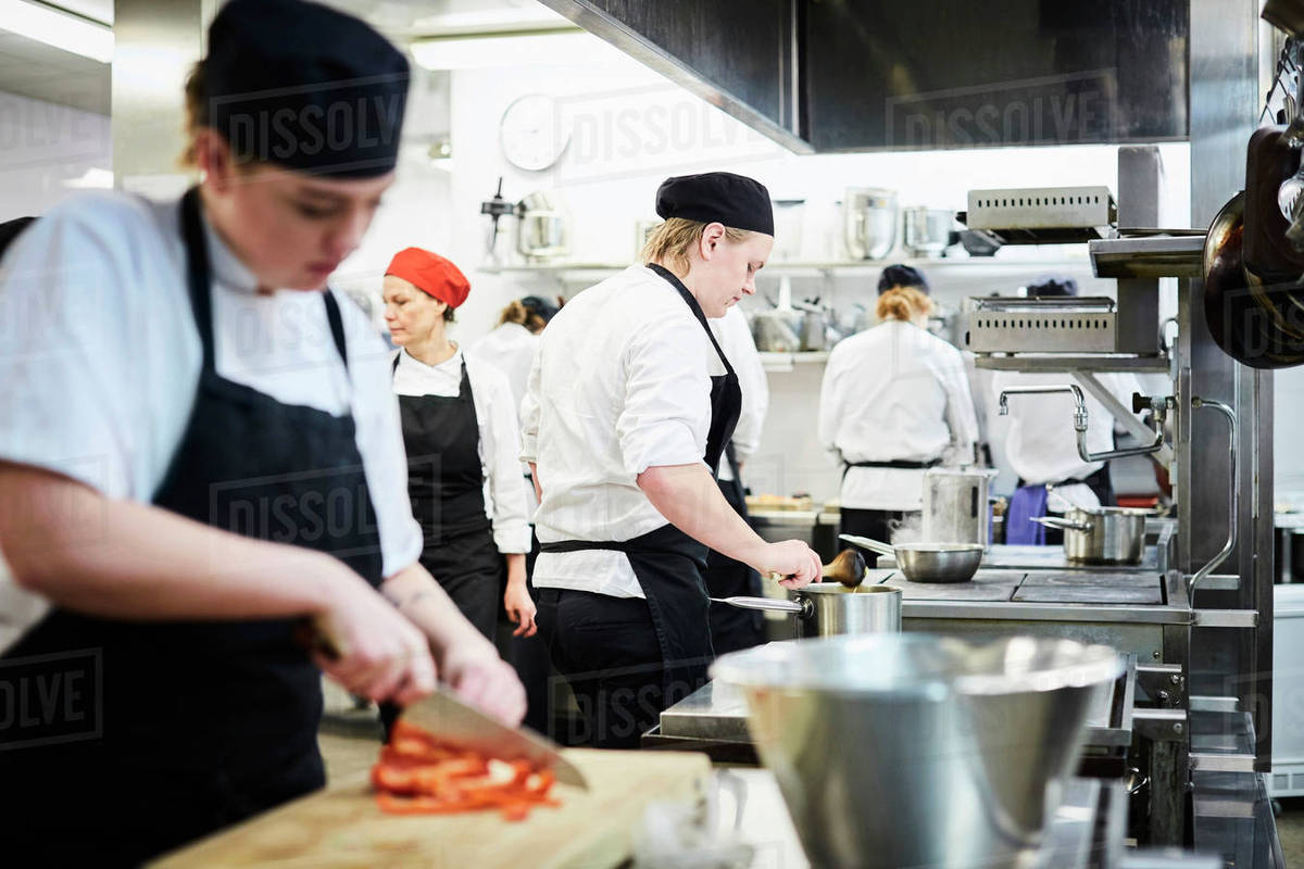 Mature teacher with chef students cooking in commercial kitchen ...