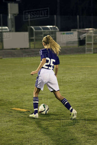 Rear view of girl playing soccer on field at night Royalty-free stock photo