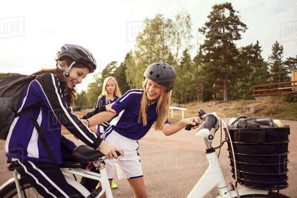 Cheerful friends enjoying with bicycle on footpath Royalty-free stock photo